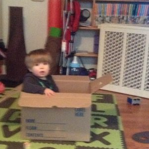 Helping to pack the 'bye-bye box' with old toys