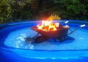 A wheelbarrow with a bonfire inside is parked in an inflatable pool.