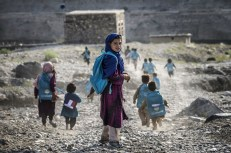Afghan children run to school on September 24, 2012, in a village on the road to Naghlu, near the French army base. (Jeff Pachoud/AFP/Getty Images)