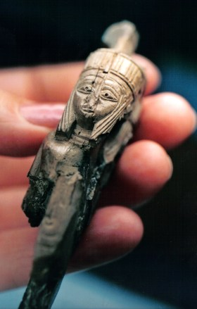 woman's hand holding a tiny broken sculpture of a lady