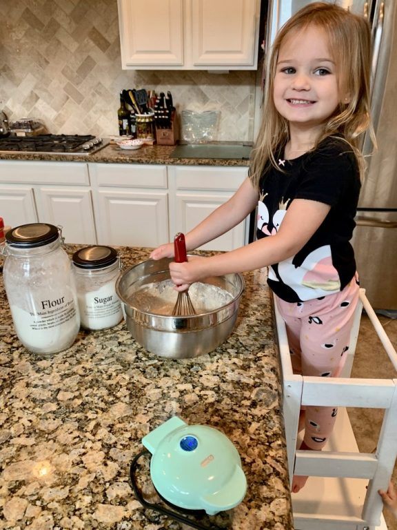 Toddler cooking waffles with mom. Flour and sugar jars. Mini waffle maker.
