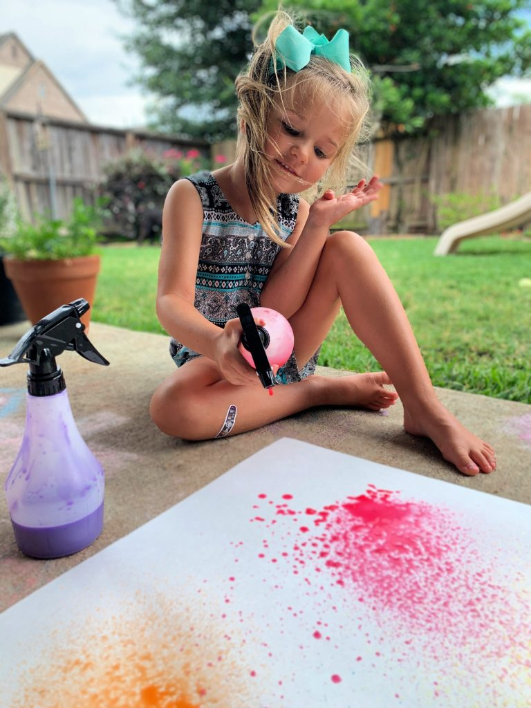 Toddler doing spray bottle summertime art project.