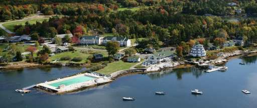 An overhead view of a seaside resort in Maine. A lighthouse, pool, boats, and beautiful autumn grounds are shown.