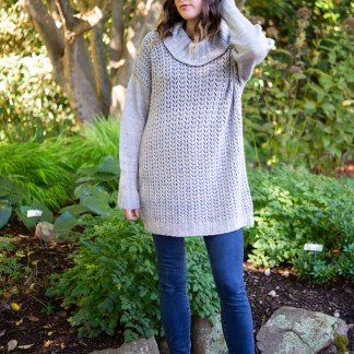 Woman in a wooded area wearing a light gray drop shoulder sweater with a lace pattern on the body, loosely fitting