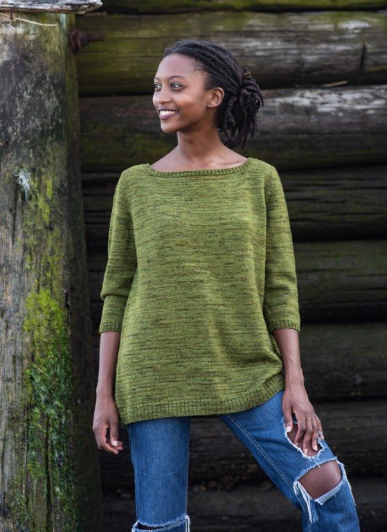 A woman wearing a variegated green hand-knit pullover, with a boat neck, well-fitting shoulders, and lots of positive ease through the body.