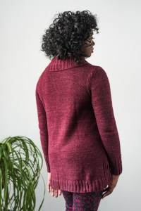 A woman wearing a deep red a-line tunic, shown from the back.