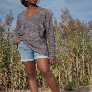 Woman on a beach wearing a loosely-fitting gray textured drop shoulder pullover