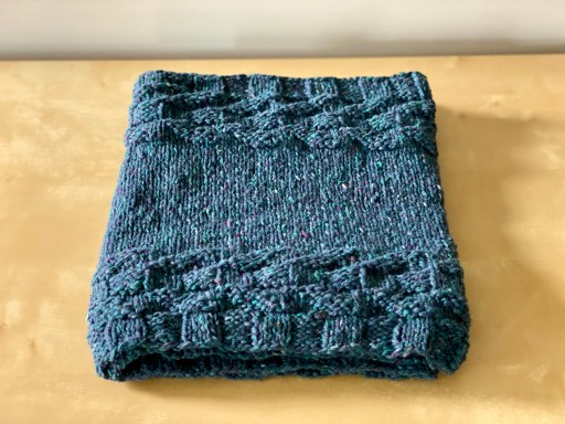 A deep blue, tweedy cowl with gansey-esque stitch patterning at each edge.