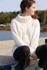 A woman, seated, in a drop shoulder turtleneck with lace patterning at the neck.