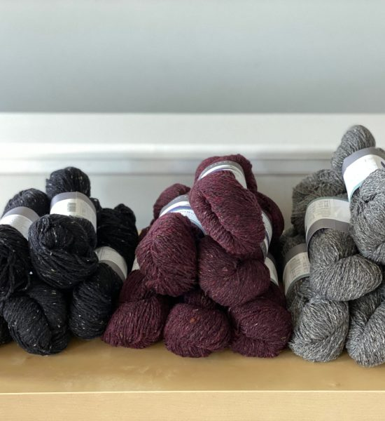 Three sweater quantities of yarn, in black, burgundy, and gray.