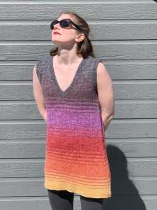 A sun-washed brunette in large sunglasses, wearing a hand-knit V-neck tunic tank that's worked in gradient stripes. It starts with a brownish-purple at the top, and progresses through purple, red, orange, before finishing in yellow at the bottom.