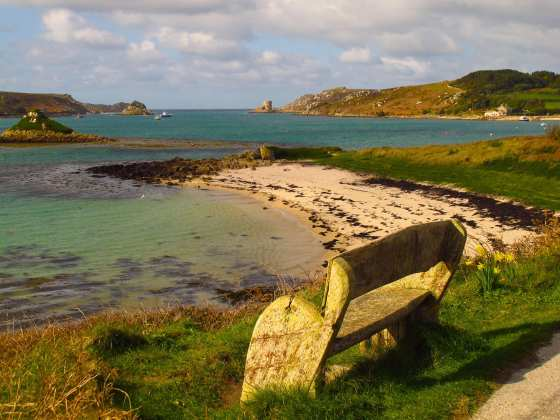 A bench on Tresco on the Isles of Scilly overlooks teal blue waters.