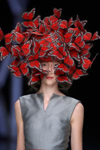 Model wearing a hat that looks like a flock of butterflies