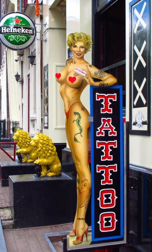 life-sized cutout sign of nearly naked pin-up posing next to a tattoo sign in Amsterdam, the Netherlands