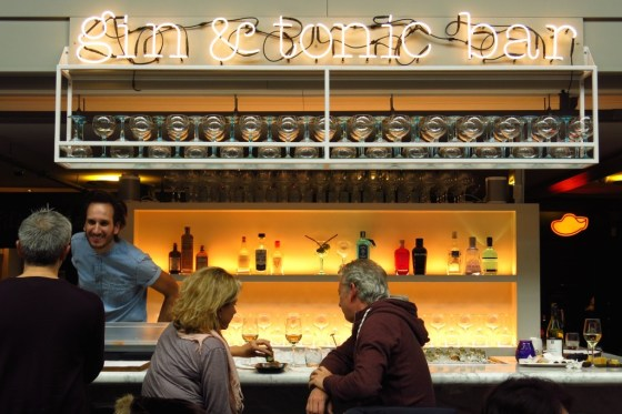 Two people sit at a counter at the Gin & Tonic Bar in De Hallen, Amsterdam