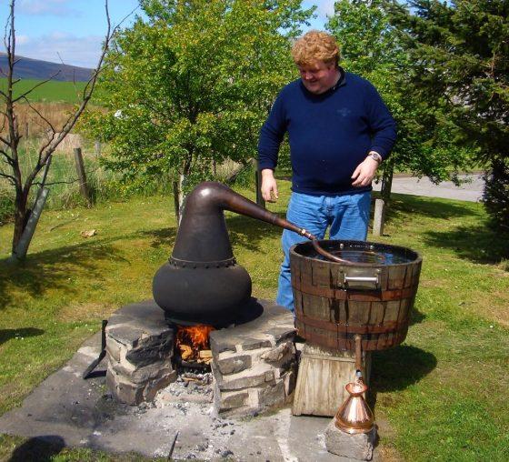 man distilling whisky at an outdoor still