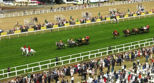 Queen Elizabeth II rides into Royal Ascot in a horse-drawn carriage.
