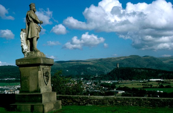 LOOKING OUT ACROSS THE TOWN OF STIRLING AND OVER TO THE WALLACE MONUMENT AND OCHIL HILLS FROM THE BATTLEMENTS OF THE CASTLE, WITH THE STATUE OF ROBERT THE BRUCE IN THE FOREGROUND, STIRLING. PIC: P.TOMKINS/VisitScotland