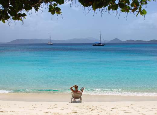 A woman relaxes on a sandy beach with a book on St. John, USVI. Copyright Amy Laughinghouse.