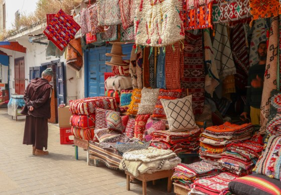 A man in a traditional Moroccan djellaba peruses a selection of textiles in Essaouira's medina.