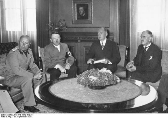 British PM Chamberlain is seen on the far right of this photo of the Munich conference participants.  From L-R are Benito Mussolini, Adolf Hitler, Paul Otto Schmidt, and Chamberlain.  Photo from the German Federal Archive