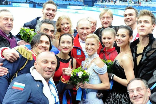 Russian president Vladimir Putin poses with members of the gold medal winning Russian figure skating team. (He's the guy in the middle of all those hot ladies.) Official Russian presidency photo