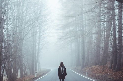 Girl standing in the middle of a foggy road, looking off in a different direction