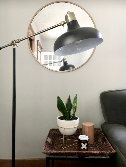round mirror, black lamp and wax buffalo candle