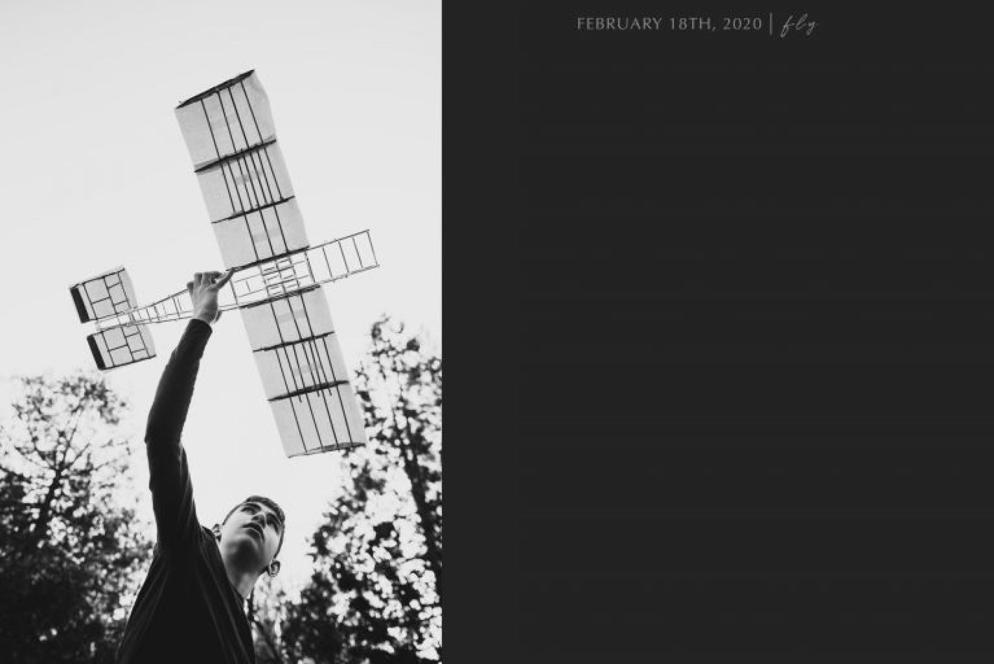 black and white photo of boy lifting a homemade airplane in the air