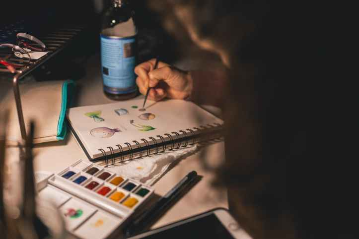 person writing illustration in spiral notebook