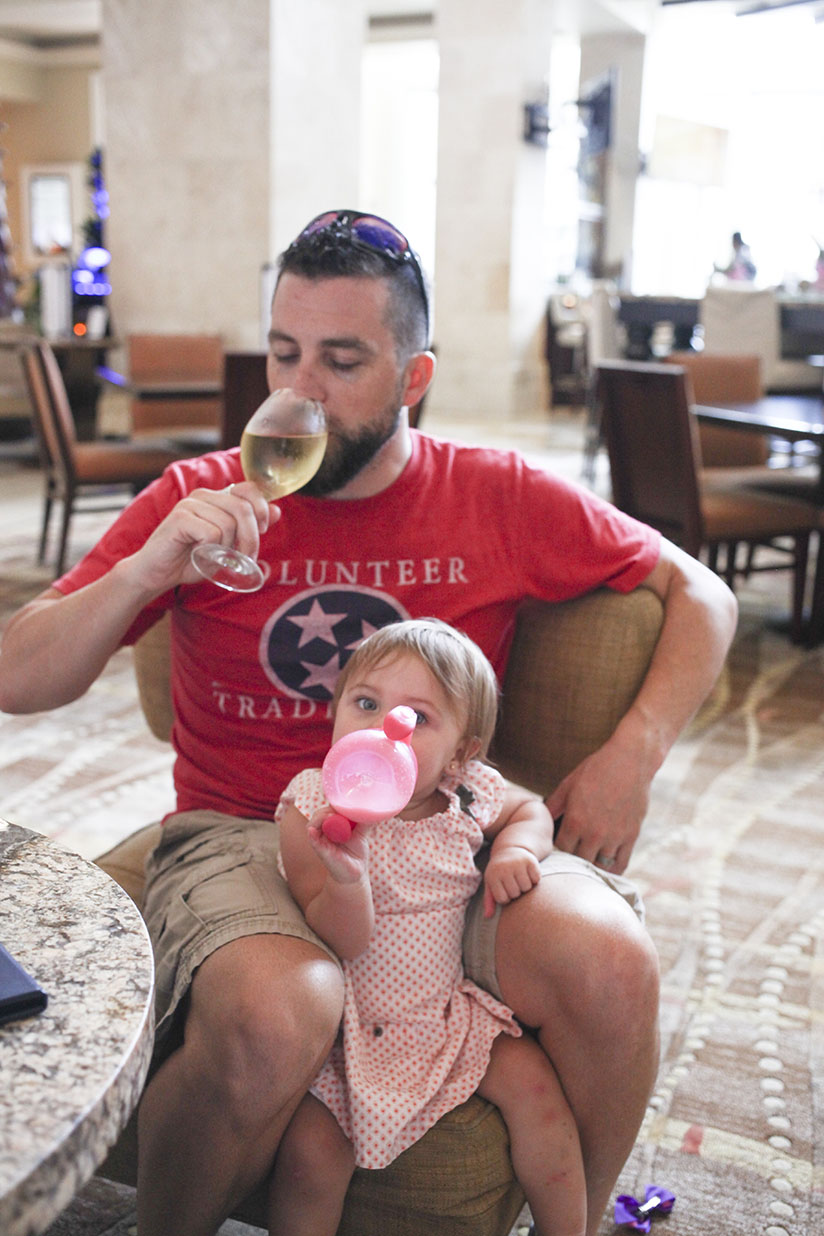 Dad drinks wine while baby drinks milk