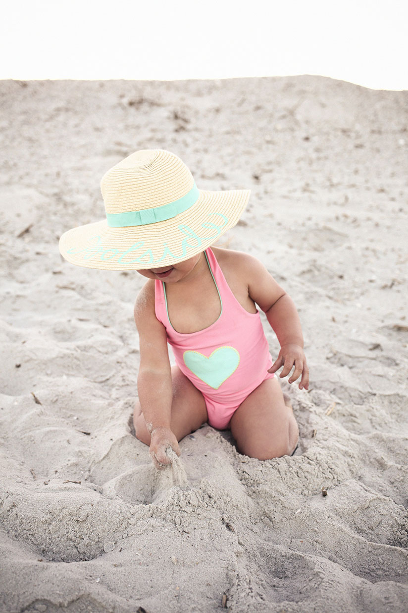 Little girl playing at the beach in reversible swimwear by Sunuva