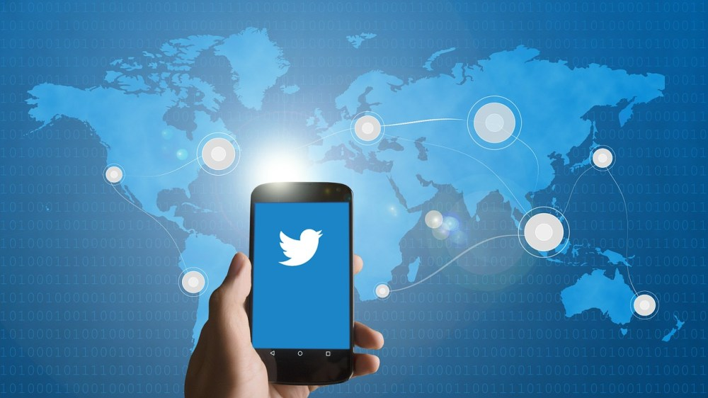 Twitter on a smartphone above the world