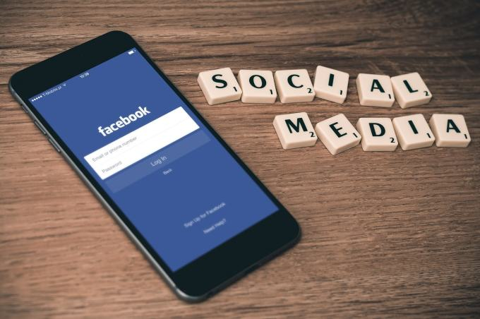 """Image of Facebook on a phone with """"social media"""" scrabble letters."""