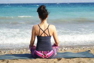 Woman reflecting on a beach.