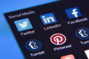 Social media icons shown on a mobile phone.