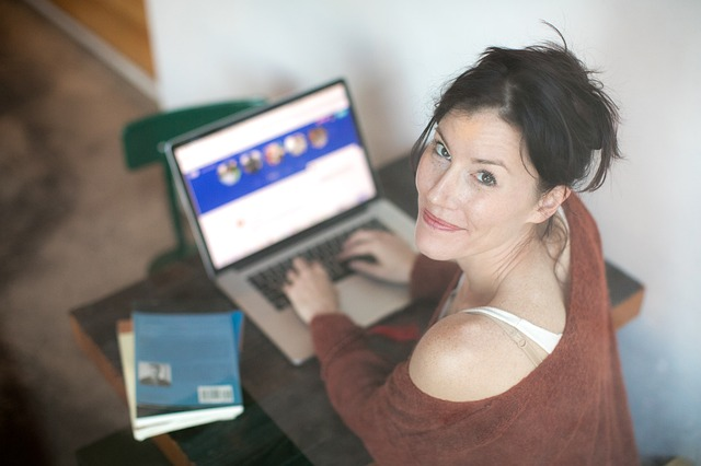 Image of a happy woman on her computer to illustrate how to come up with blog post ideas.