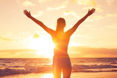 Happy Free Woman at Sunset on the Beach