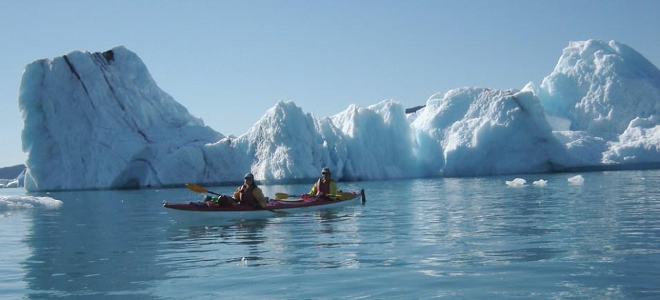 Floating through huge icebergs in kayak