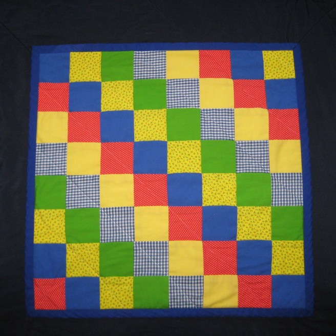 Photograph of front of baby quilt showing cobalt blue binding and front pieced in squares of red, blue, yellow, and green fabrics