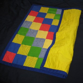 Photograph of folded baby quilt showing cobalt blue binding, solid yellow backing, and front pieced from squares of red, blue, green, and yellow fabrics