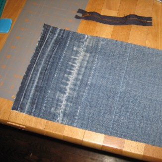 Rectangle of denim, closely quilted in straight lines, on table with sewing supplies