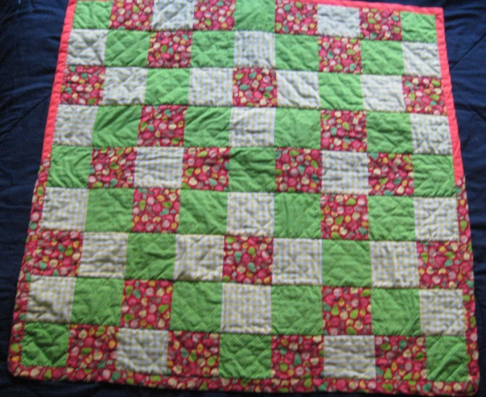 Photograph of front of baby quilt featuring green, red, and yellow squares and red binding