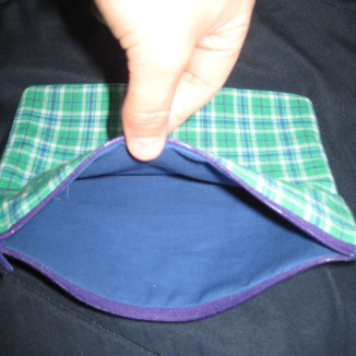 Photograph of green plaid zip pouch showing blue interior