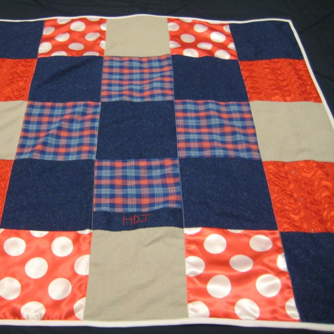 Photograph of baby quilt made from squares of red, blue, and gray fabrics and bound in white