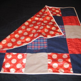 Photograph of baby quilt made from squares of red, blue, and gray fabrics and bound in white, with corner folded over to reveal backing of red satin with white polka dots