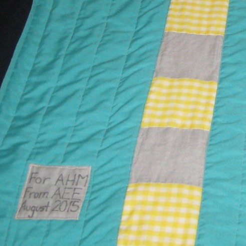 Detail photo of aqua, yellow, and gray baby quilt showing quilt label