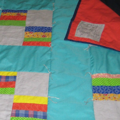 Detail photo of aqua and multi-colored baby quilt showing quilt label