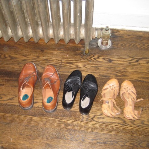 Photograph of three pairs of shoes on the floor next to a radiator