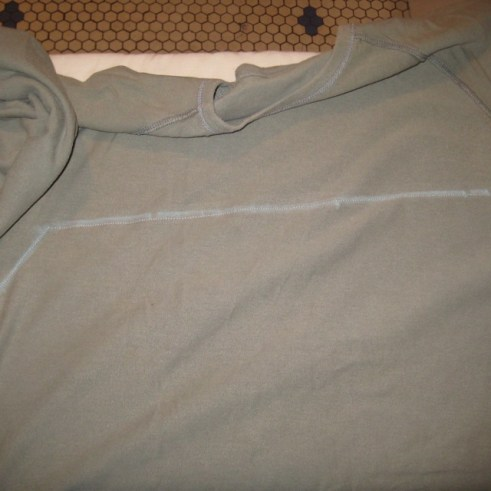 Photograph of sage green shirt with stitching along chalk markings